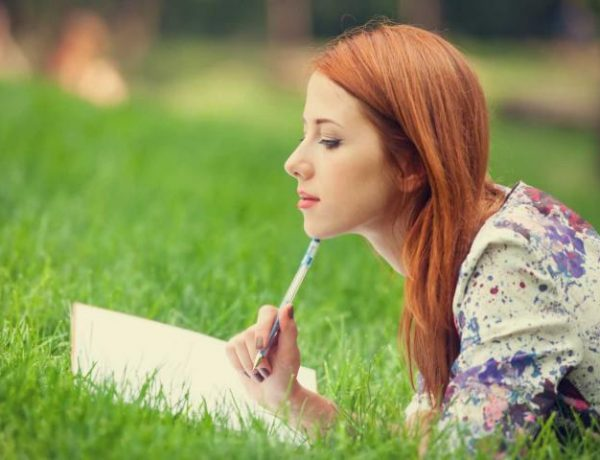 A woman sitting in a field writing in a notebook